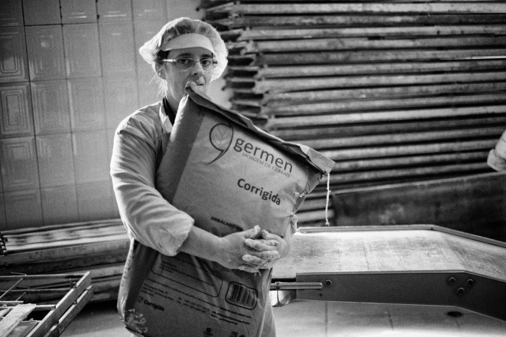 At roughly 9:00 AM. Márcia Carvalho carries a bag of flour from the warehouse to the mixing machine. Por volta das 9:00 da manhã. Márcia Carvalho carrega um saco de farinha do armazém para a máquina de misturar.