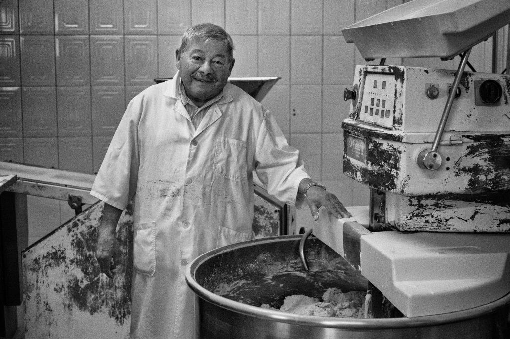 Fernando Carvalho, the owner and founder of the bakery, poses for a portrait by the dough mixing machine. Fernando Carvalho, proprietário e fudador da padaria, posa para um retrato junto à máquina de misturar massa.