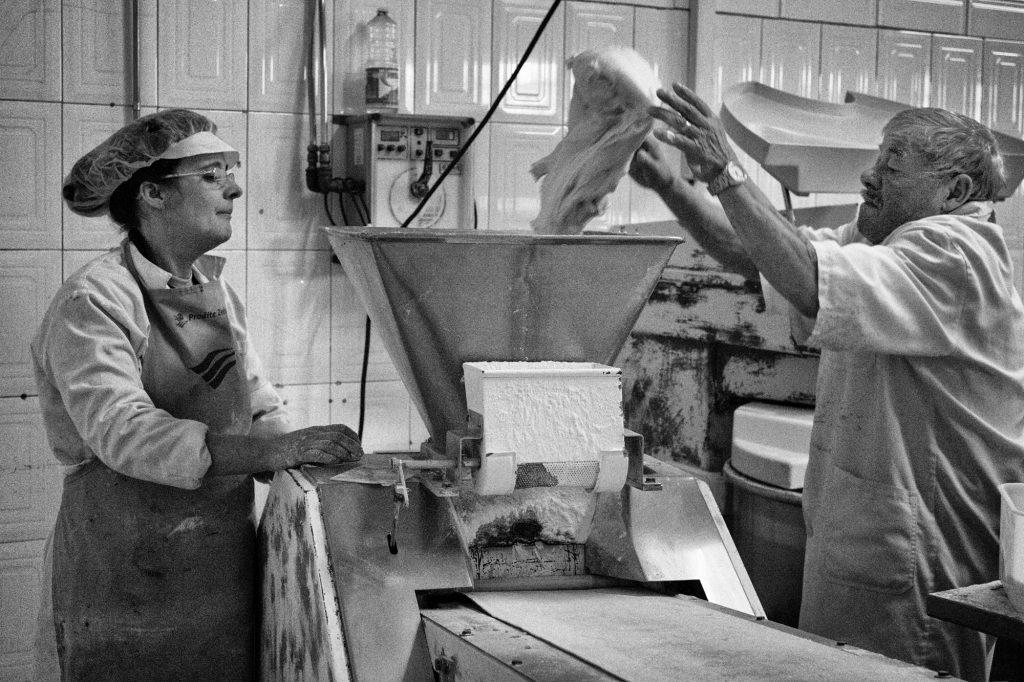 Márcia Carvalho watches Fernando Carvalho throw a chunk of dough into the scale and splitting machine. Márcia Carvalho observa Fernando Carvalho atirar um pedaço de massa para dentro da máquina de pesar e dividir.