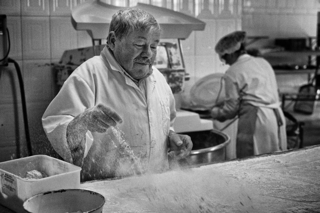 Fernando Carvalho prepares the workbench by sprinkling it with flour. Fernando Carvalho prepara a mesa de trabalho borrifando-a com farinha.