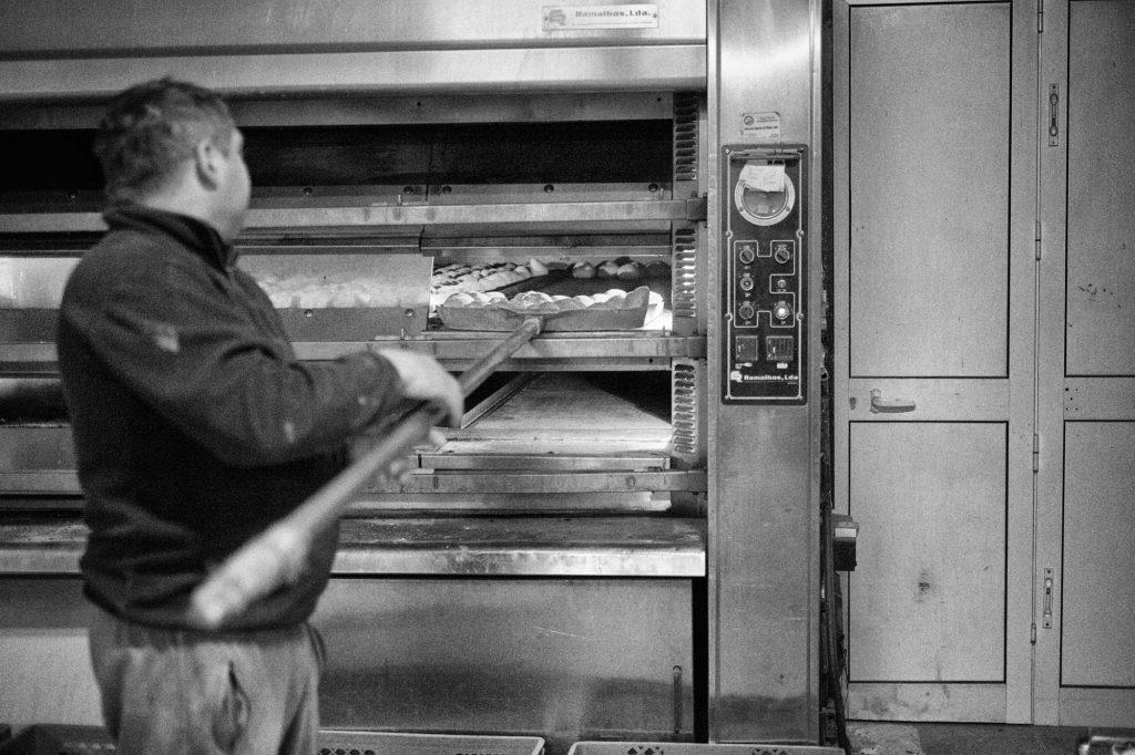 Rui Carvalho takes the baked bread out of the oven. He tells me about other more industrialized bread factories where in one hour is produced more than 10 times of his daily production. Rui Carvalho retira uma fornada de pão do forno. Ele conta-me histórias de fábricas de pão onde numa hora se produz mais de 10 vezes do que ele produz num dia inteiro.